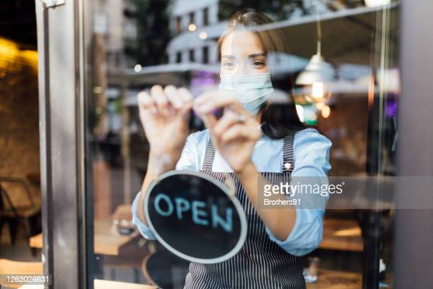 young waitress opening a cafe - reopening stock pictures, royalty-free photos & images