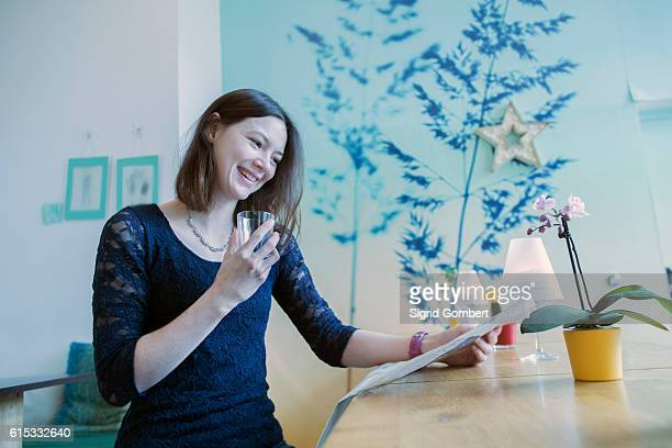 young waitress reading paper and smiling with glass at coffee shop counter, freiburg im breisgau, baden-württemberg, germany - sigrid gombert 個照片及圖片檔