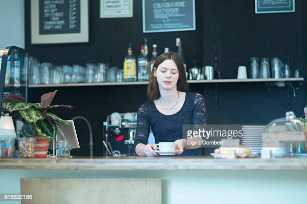 young waitress serving coffee in coffee shop, freiburg im breisgau, baden-württemberg, germany - sigrid gombert stock pictures, royalty-free photos & images