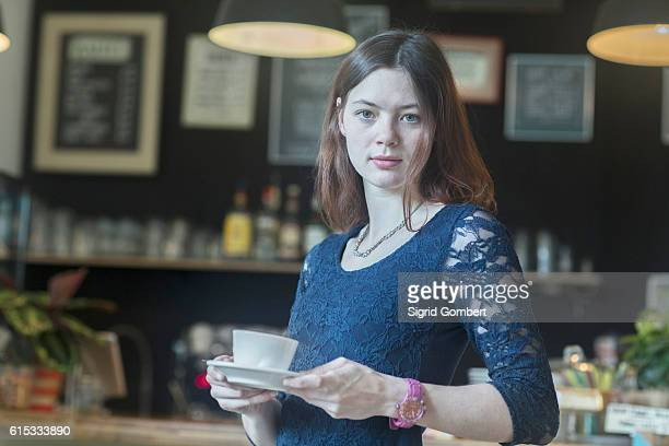 young waitress serving coffee in coffee shop, freiburg im breisgau, baden-württemberg, germany - sigrid gombert stock-fotos und bilder