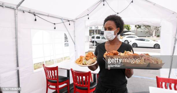 young waitress serving food to customers in outdoor tent wearing a mask - adamkaz stock pictures, royalty-free photos & images