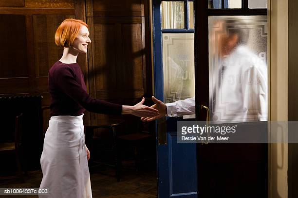 Young waitress shaking hand with businessman entering bar, smiling, side view