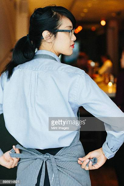 Young waitress tying her apron at a city restaurant.