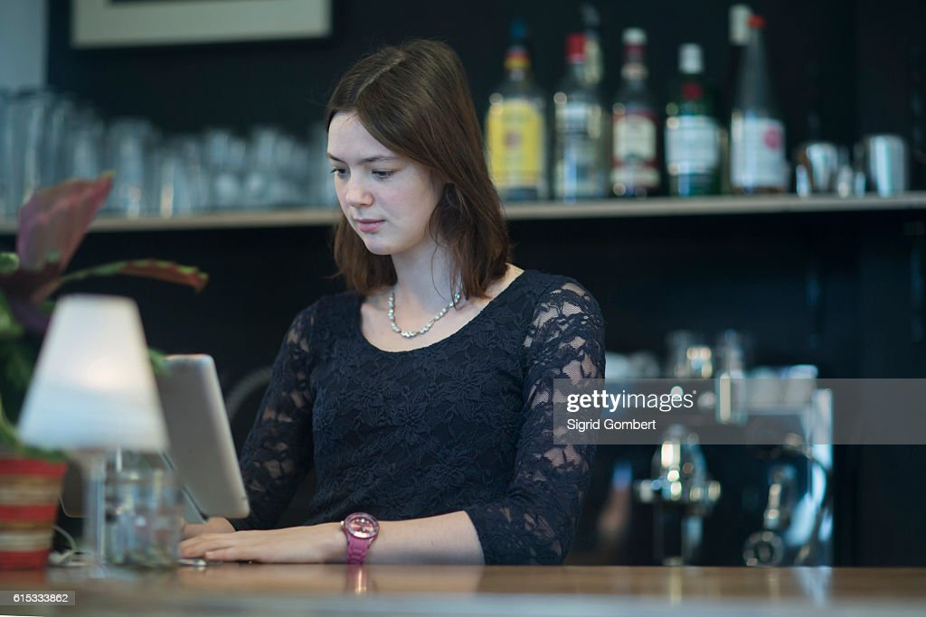 Young waitress using computer in coffee shop at checkout counter, Freiburg Im Breisgau, Baden-Württemberg, Germany : Stock-Foto