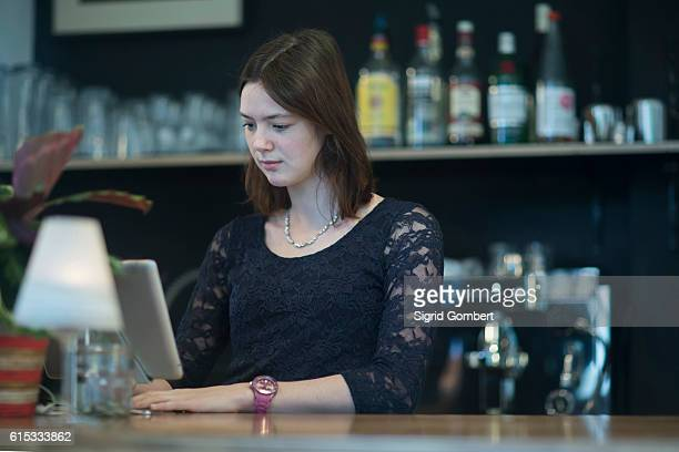 young waitress using computer in coffee shop at checkout counter, freiburg im breisgau, baden-württemberg, germany - sigrid gombert stock pictures, royalty-free photos & images