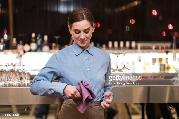 Junge Kellnerin putzt ein Weinglas