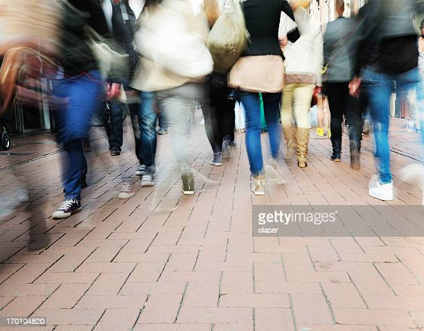 Young walking on street, motion blur