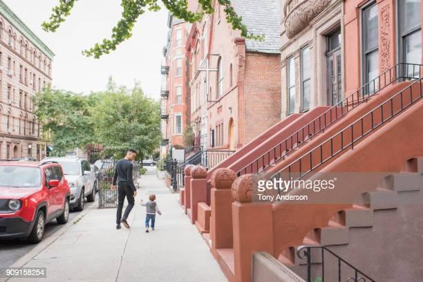 Young walking with infant daughter in their city neighborhood