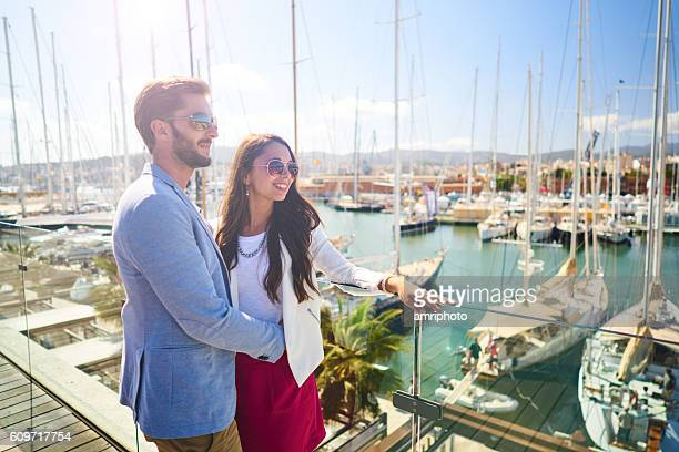 young wealthy couple standing on marina - palma majorca stock photos and pictures