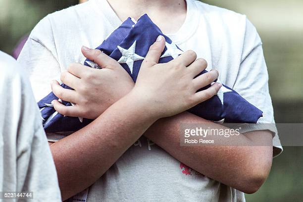 a young weblo boy scout holding a folded american flag in camp - robb reece stockfoto's en -beelden