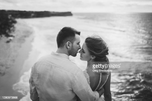 young wedding couple in love kissing outdoors with amazing ocean view in bali - marriage stock pictures, royalty-free photos & images