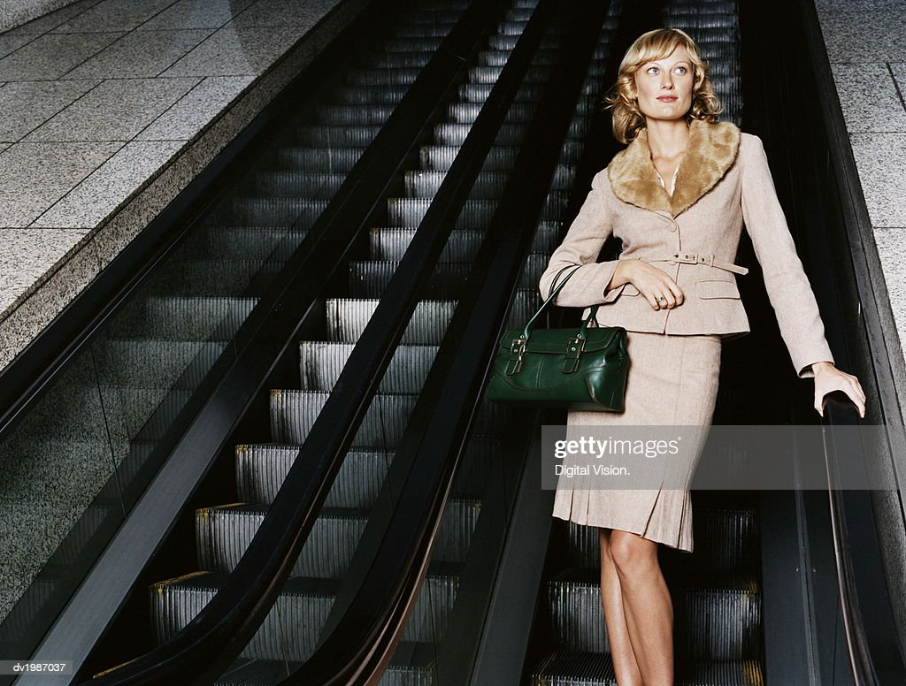 Young, Well Dressed Woman Standing on an Escalator : Stock Photo