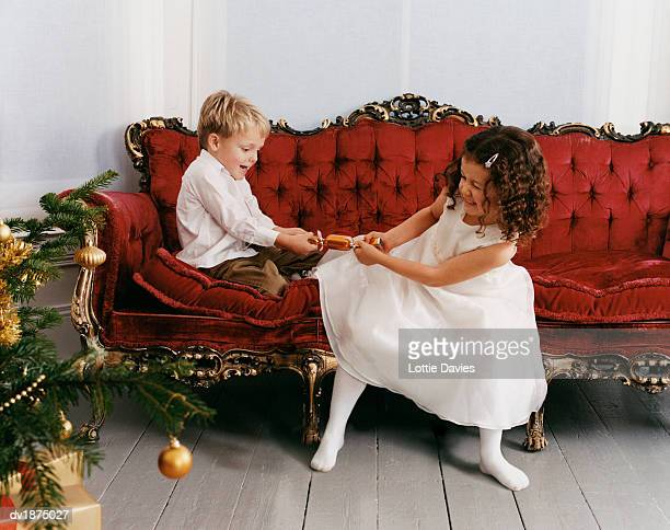 young, well-dressed boy and girl sit on an ornate sofa, pulling a christmas cracker - boys wearing tights stock photos and pictures