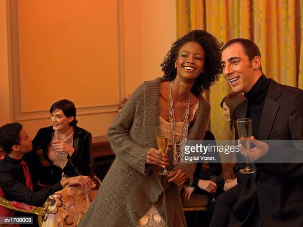 young, well-dressed man and woman stand side by side at a dinner party holding champagne flutes and laughing - goed gekleed stockfoto's en -beelden