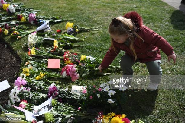 Young well-wisher adds flowers to the tributes and messages of condolence outside Windsor Castle in Windsor, west of London, on April 11 two days...
