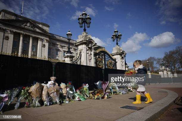 Young well-wisher adds flowers to the tributes outside Buckingham Palace in central London, on April 11 two days after the death of Britain's Prince...