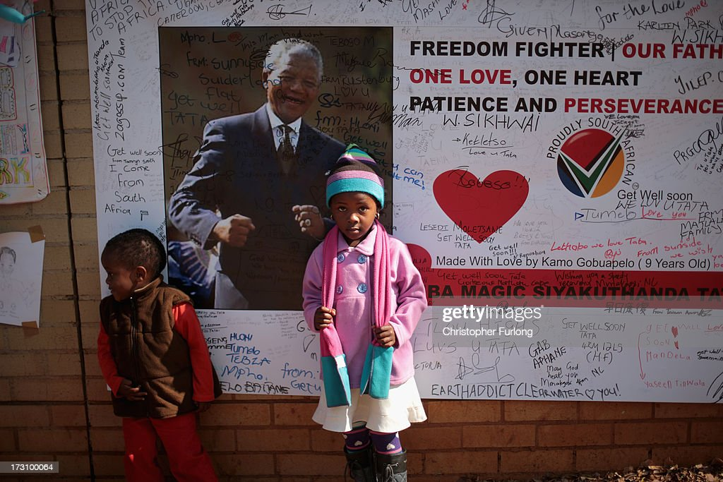 Young well-wishers pose for a family photograph as they gather to pay tribute to former South African President Nelson Mandela at the memorial wall at the Medi-Clinic Heart Hospital l on July 7, 2013 in Pretoria, South Africa. Mandela has been hospitalized at the Medi-Clinic Hospital since June 8 for treatment for a recurring lung infection.