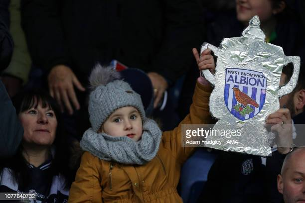 A young West Bromwich Albion Fan holds up a tinfoil / bacofoil cut out of the FA Cup during the FA Cup Third Round match between West Bromwich Albion...