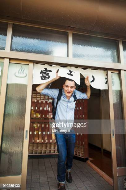 A young Western man coming out of a public bath house, ducking under the entrance sign.