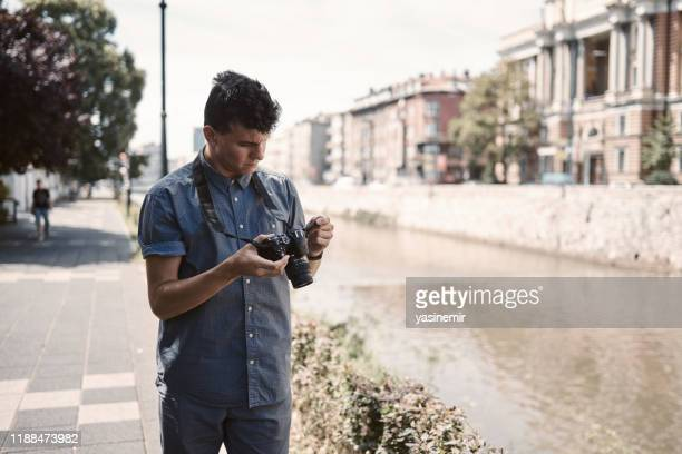 young white photographer disappoints after checking photos on camera. sunny day in old town. - sarajevo stock pictures, royalty-free photos & images