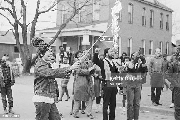 A young white woman burns a Confederate battle flag to the cheers of you African American men during a protest outside Brown's Chapel AME Church in...