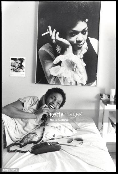 A Young Whitney Houston is pictured in her bedroom on the telephone beneath a poster of her mother circa 1982 in West Orange New Jersey