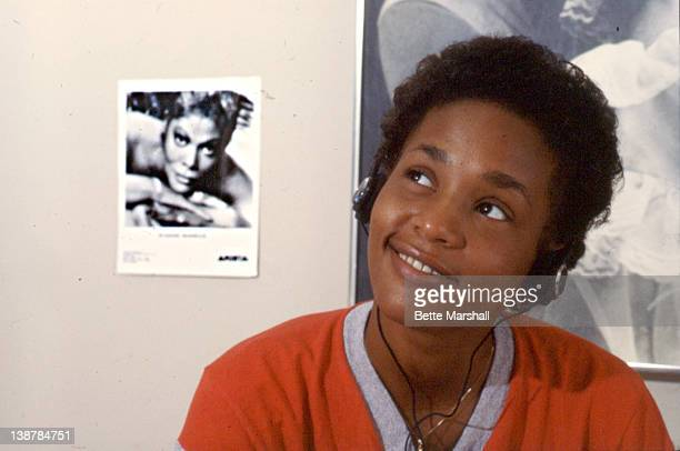 A Young Whitney Houston is seen pictured during a portrait session circa 1982 in her home in West Orange New Jersey The photo in the background is...