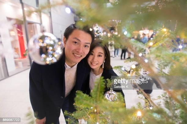 Jeune femme et du mari, regardant la caméra à travers l'arbre de Noël