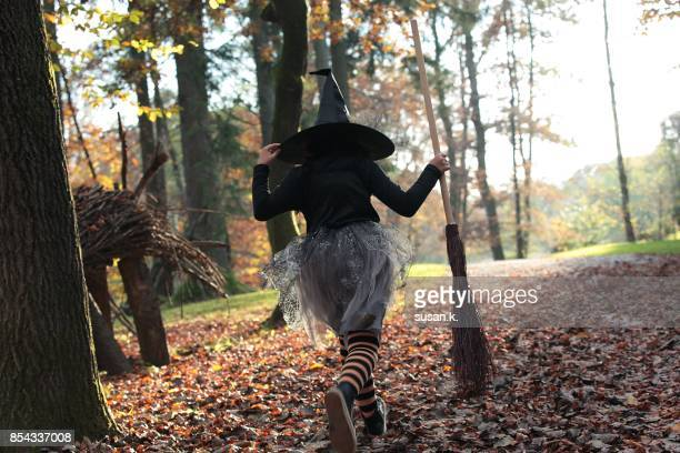 young witch is running in the forest. - hexe stock-fotos und bilder