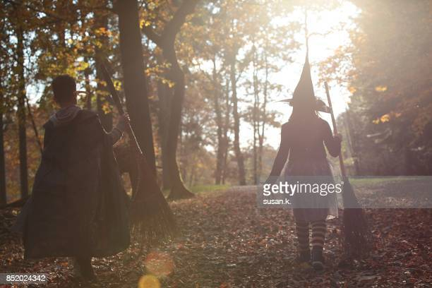 Young wizard and witch walking into the light in the forest.