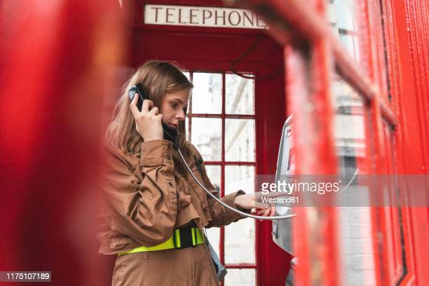 young woma nmaking a call from a red phone booth in the city, london, uk - telephone number stock pictures, royalty-free photos & images