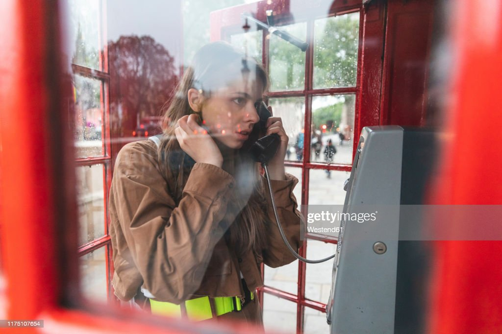 Young woma nmaking a call from a red phone booth in the city, London, UK : Stock Photo