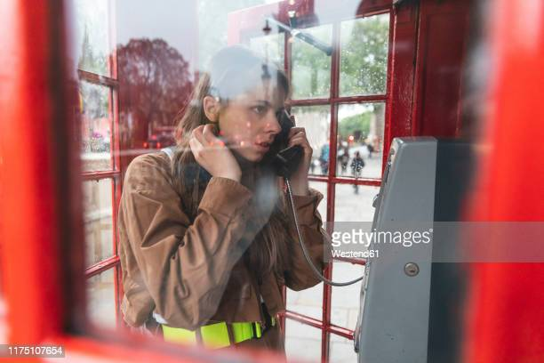 young woma nmaking a call from a red phone booth in the city, london, uk - red telephone box stock pictures, royalty-free photos & images