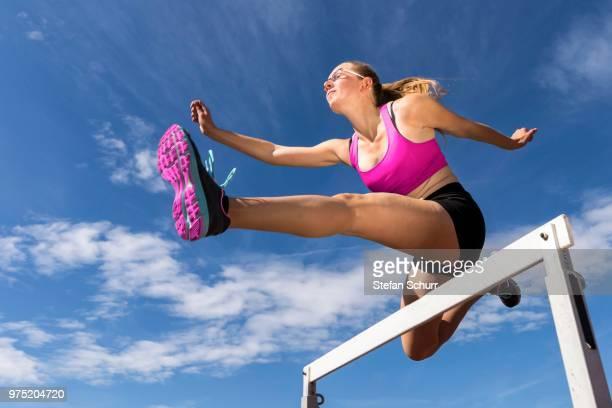 Young woman, 18 years, hurdling