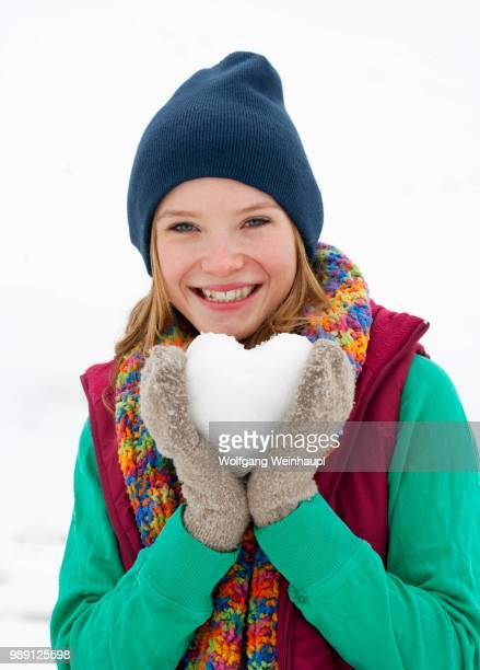 Young woman, 22 years, holding a heart made of snow