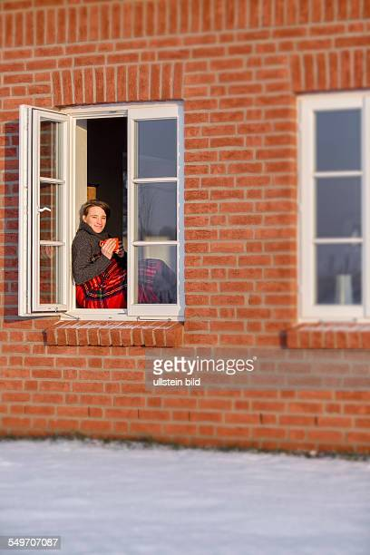Young woman 35 years sitting in the winter with a warm drink and a blanket in a window