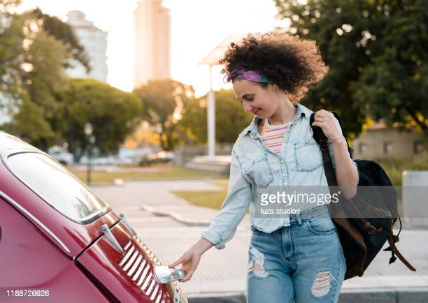 young woman about to put her backpack into the car trunk - open backpack stock pictures, royalty-free photos & images