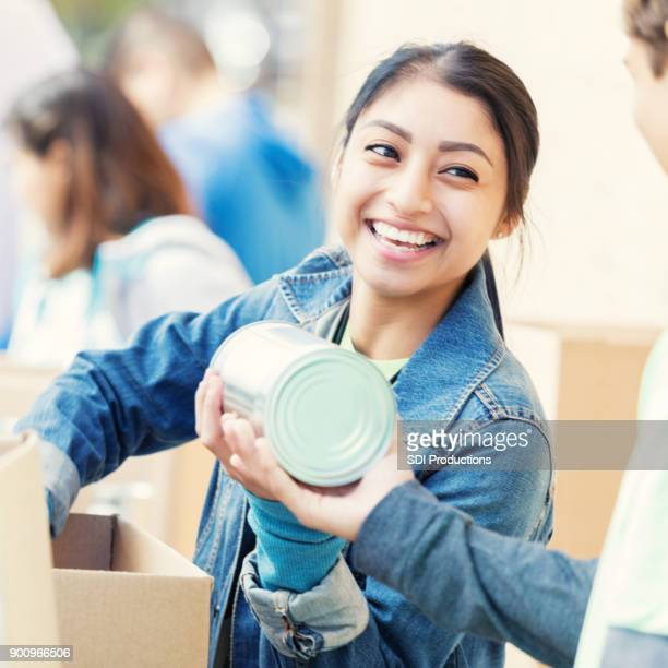 young woman accepts canned food donation during food drive - food pantry stock pictures, royalty-free photos & images