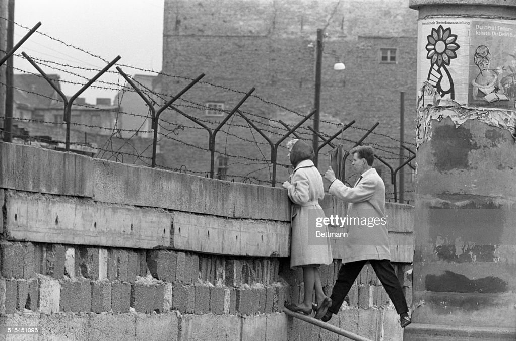 Young Couple Peers Over Berlin Wall : News Photo