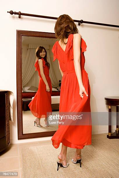 Young woman adjusting dress in front of mirror