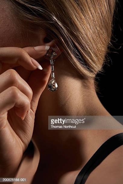 Young woman adjusting earring, side view