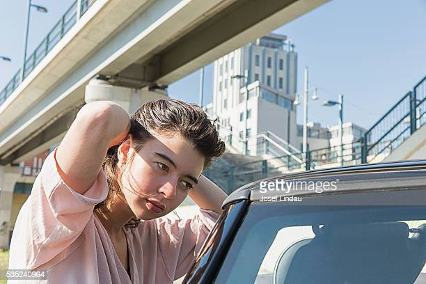 Young woman adjusting her hair in car mirror