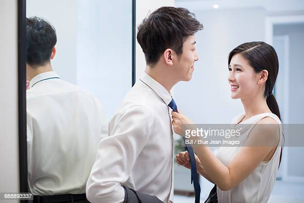 Young woman adjusting husbands tie