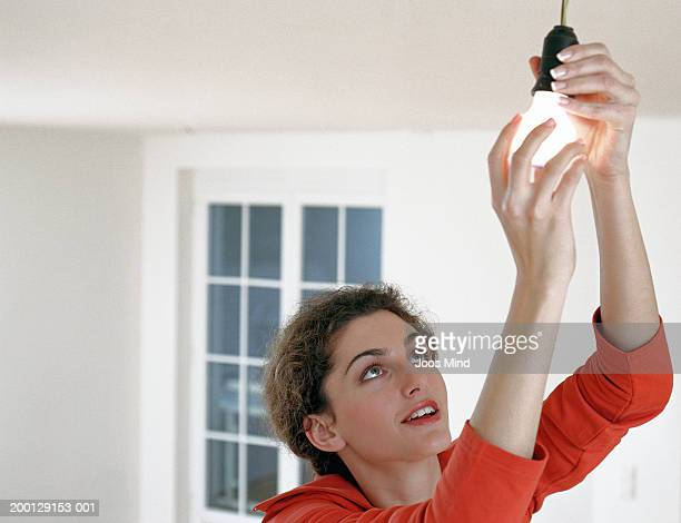 Young woman adjusting illuminated light bulb in fitting