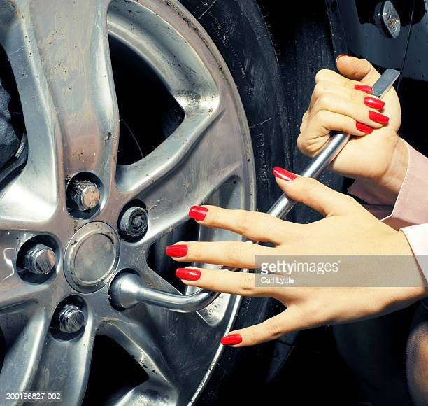 Young woman adjusting nut on wheel hub, close-up