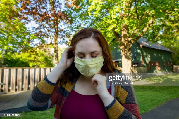 young woman adjusting protective face mask - adjusting stock pictures, royalty-free photos & images