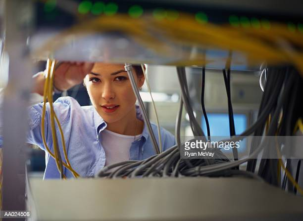 Young woman adjusting server cable