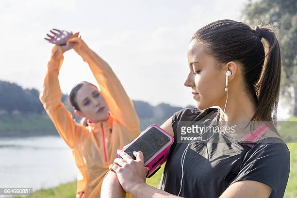 Young woman adjusting smartphone, attached to arm, for exercising