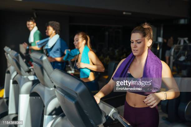 Young woman adjusting speed on a treadmill at gym