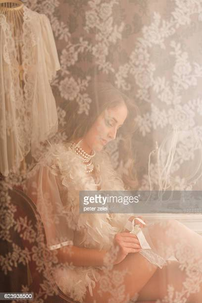 young woman adjusting stockings - lace textile stock pictures, royalty-free photos & images